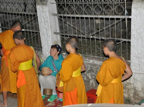 Dawn alms for the monks.  Sticky rice from my bamboo pot to their metal pot in a leather sling.