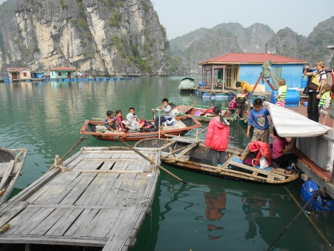 School is out in the floating village.  1st, 2nd and 3rd graders jump in boats and head home.